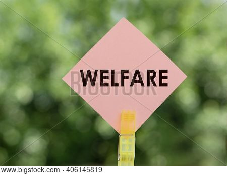 The Word Welfare On Pink Note Paper On Green Background.