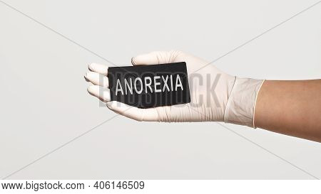 Closeup Of The Hand In A White Sterile Glove Holding A Card With Word - Anorexia. Medical Concept