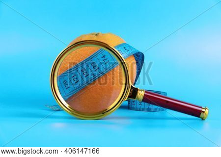 Magnifying Glass, Tape Measure And Orange On A Blue Background As A Symbol Of Cellulite. Anti-cellul
