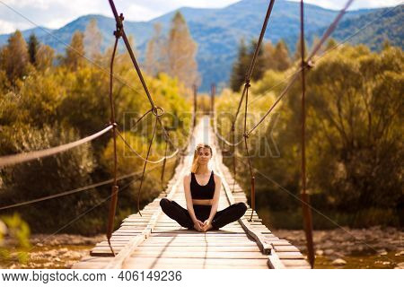 Portrait Of Calm Girl Practicing Yoga Meditation Sitting In Lotus Pose On Bridge Over Mountain River