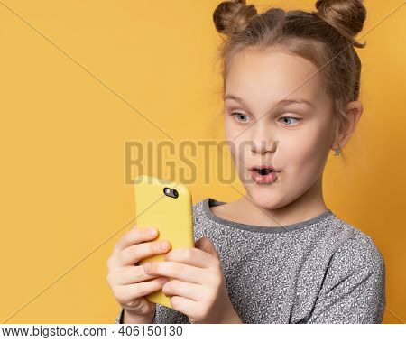 Portrait Of Excited Beautiful Girl Playing Games On Mobile Phone Isolated On Yellow Background