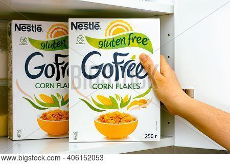 Tambov, Russian Federation - January 25, 2021 Woman Hand Taking Nestle Gluten Free Corn Flakes Box O