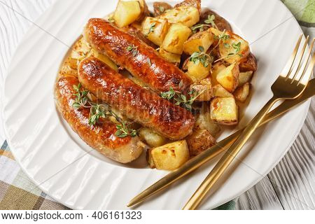 Bangers And Roasted Potatoes On A White Plate With Onion Gravy In A Jug On A White Textured Wooden T