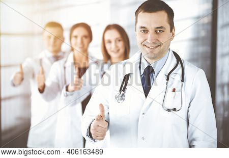 Group Of Professional Doctors Are Standing As A Team With Thumbs Up In A Sunny Hospital Office, Read