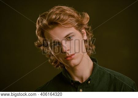 Portrait of a handsome young man with wavy blond hair on a dark background. Men's beauty.