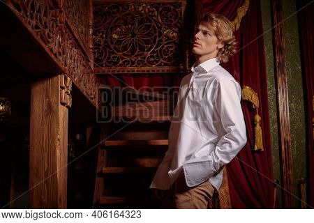 Portrait of a handsome young man with wavy blond hair wearing elegant white shirt in a luxury apartments with classic interior. Men's beauty, fashion.
