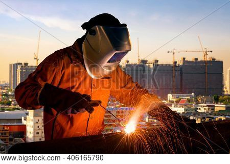 Industrial Worker Welding Steel Structure For Infrastructure Building Project With Construction Site