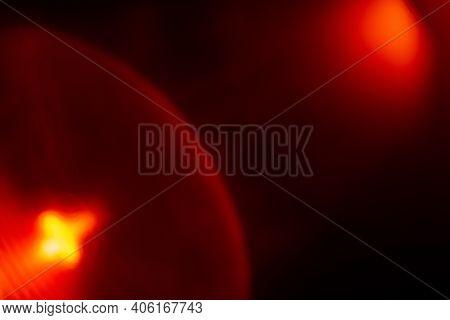 Lens Flare. Blur Radiance. Light Refraction. Red Orange Defocused Spotlight Glow Flecks On Dark Blac