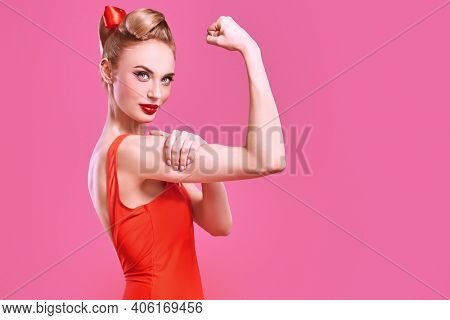 Pin-up beauty girl. Portrait of a pretty blonde woman with make-up and hair in pin-up style showing her strength on a pink background. Valentine's Day. Copy space.