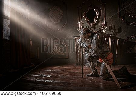 Medieval knight in armor knelt down and reads a prayer in the castle before the battle.