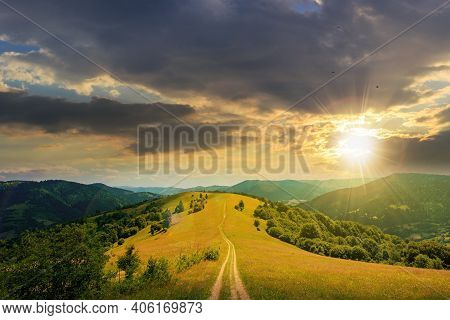 Road Through Meadow In Mountains At Sunset. Beautiful Rural Landscape Of Carpathians In Evening Ligh