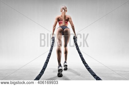 Sports Girl Trains With Ropes. Back View. The Concept Of Sports, Fitness, Aerobics, Bodybuilding, St