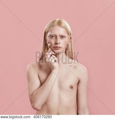 Young Caucasian Man With Long Blond Hair Massaging Cheek Using Quartz Roller While Standing On Pink