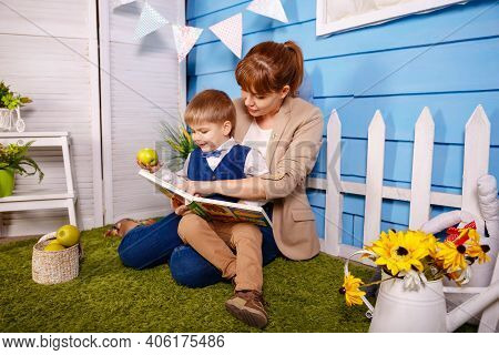 Family Before Going To Bed Mother Reads Child A Book In The Evening. Mother Reading To His Kid On Fl