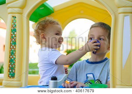 Cute Little Girl Feeding His Brother