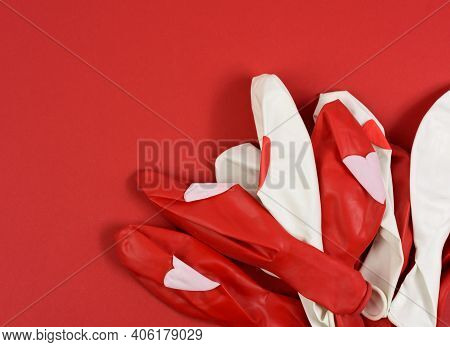Deflated Red And White Balloons On A Red Background, Top View