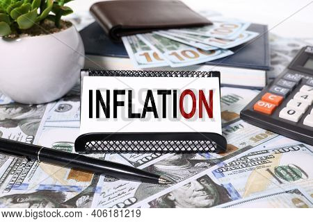 Inflation, Text On White Paper In A Business Card Holder On A Background Of Money. And Calculator