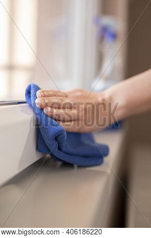 Detail Of Female Hands Wiping Windows With A Cleanser Spray And A Cloth; Housekeeping Assistant Wipi