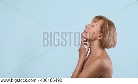 Graceful Aging Concept. Beautiful Senior Lady Touching Skin On Her Neck Over Blue Studio Background.
