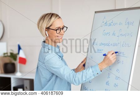 Friendly Female Teacher Writing Grammar Rules On Blackboard During Online French Lesson. Positive Yo