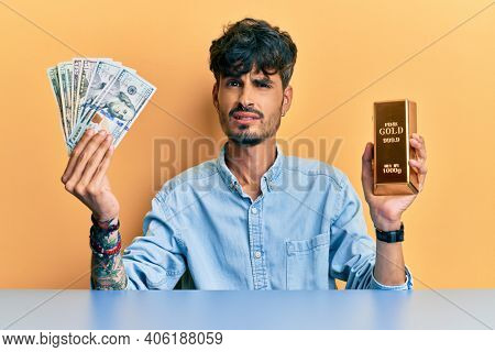 Young hispanic man holding dollars and gold ingot clueless and confused expression. doubt concept.