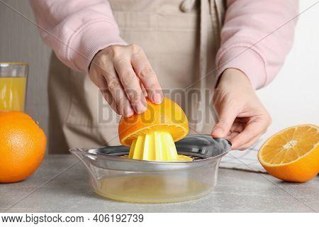 Woman Squeezing Orange Juice At Grey Table, Closeup
