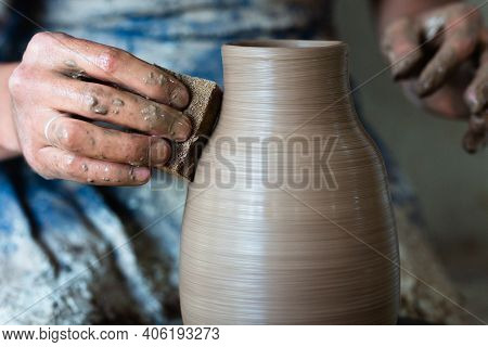 Potter Hands Making In Clay On Pottery Wheel. Potter Makes On The Pottery Wheel