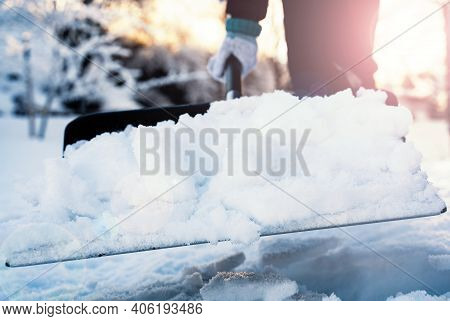 Close Up Of A Person Shoveling Snow From The Sidewalk In The Winter. Shallow Depth Of Field.