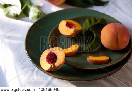 Peach In Halves With Bone. Peaches With Leaves On Color Green Plate On Table With White Tablecloth.