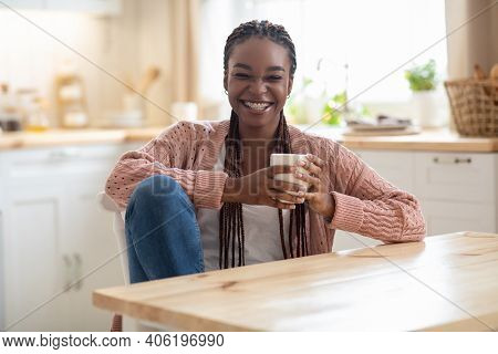 Cheerful Young African American Woman Relaxing In Cozy Kitchen, Drinking Coffee. Joyful Millennial B