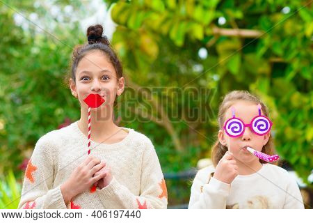 Surprised Little Girl Holding Funny Lips On Stick And Happy Girl With Cute Sunglasses And Noisemaker