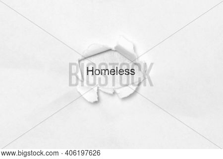 Word Homeless On White Isolated Background, The Inscription Through The Wound Hole In Paper. Concept