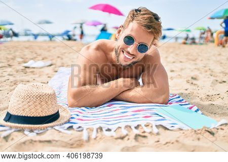 Handsome fitness caucasian man at the beach on a sunny day sunbathing lying on the towel