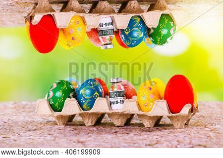 Mirror Image Of Pascal Colored Eggs Near An Ampoule Of Covid 19 Vaccine On A Cardboard Box. Green Il