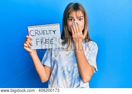 Teenager caucasian girl holding cruelty free cosmetics banner covering mouth with hand, shocked and afraid for mistake. surprised expression