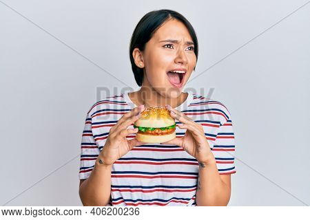 Beautiful young woman with short hair eating hamburger angry and mad screaming frustrated and furious, shouting with anger. rage and aggressive concept.