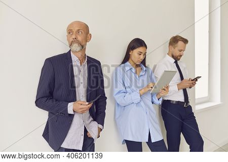 Bored, Serious Multi-aged People Lining Up In Office Waiting Area And Using Gadgets
