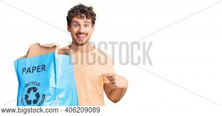 Young handsome man with curly hair holding recycling wastebasket with paper and cardboard smiling happy pointing with hand and finger