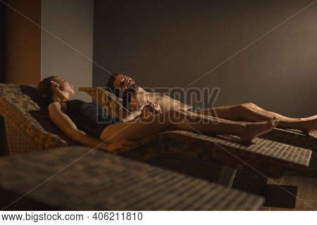 Couple In Love Relaxing In Spa Center Himalayan Salty Room, Lying On Heat Beds, Holding Hands And En