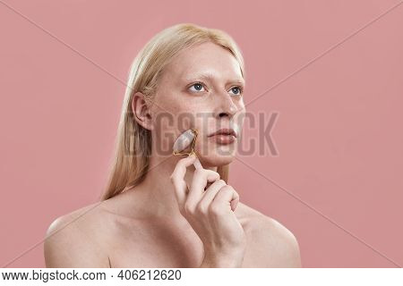 Young Caucasian Man With Long Blond Hair Massaging Cheek With Quartz Roller While Standing On Pink B