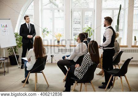 Explaining. Male Speaker Giving Presentation In Hall At University Workshop. Audience Or Conference