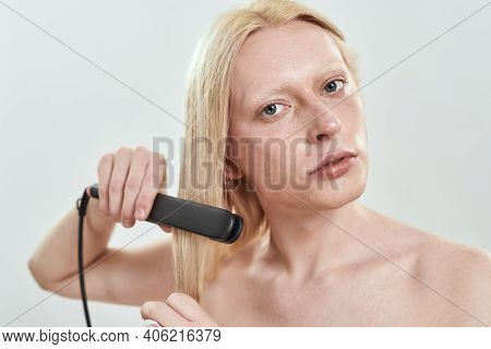 Portrait Of Young Caucasian Man Using Tool For Straightening Long Blond Hair While Standing On White