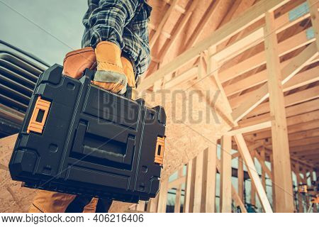 Construction Contractor With Plastic Power Tools Box In His Hand Going To Wooden Skeleton Frame Cons