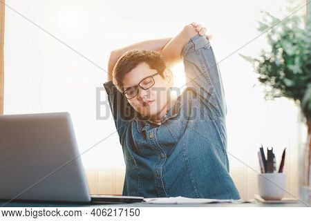 Young Businessman Exercises Stretching The Muscles At The Desk At Work, Relax From Hard Work.