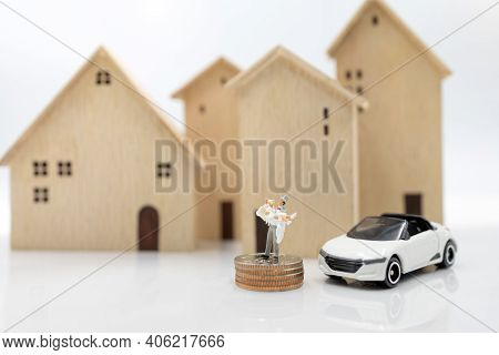 Miniature People: Couple In Wedding Dresses Stand On Coins Stack With House And Car. Family Planning