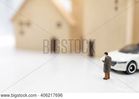 Miniature People:  Businessman Reading Book With House And Car.  Concept Of Investment In Housing An