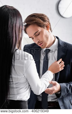 Back View Of Brunette Businesswoman Seducing Young Colleague In Office.