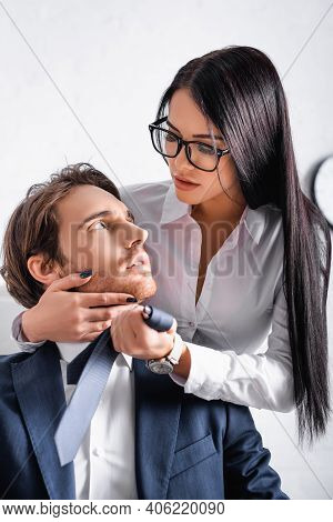 Sensual Brunette Businesswoman Touching Face Of Colleague While Seducing Him In Office.