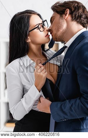 Sexy Businesswoman Pulling Tie Of Young Businessman While Seducing Him In Office.