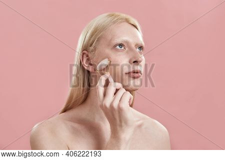 Young Caucasian Man With Long Blond Hair Massaging Face With Quartz Roller While Standing On Pink Ba